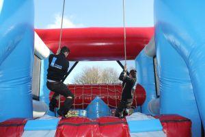 Deelnemers hindernis gaan slinger met touw naar net.